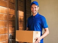 41560149-cheerful-delivery-man-happy-young-courier-holding-a-cardboard-box-while-standing-against-door-of-res-min